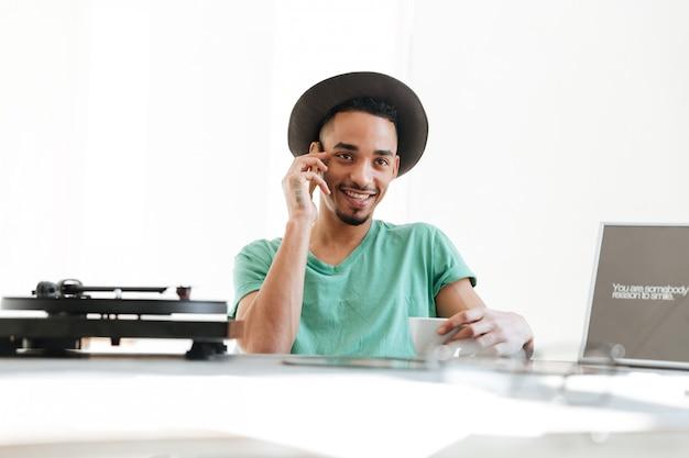 Glimlachende afrikaanse mens die op smartphone spreekt