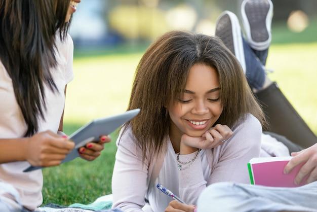 Glimlachende afrikaanse studente die in openlucht bestuderen