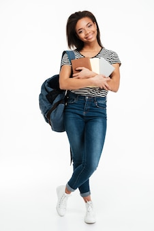Glimlachende afrikaanse tienervrouw die rugzak draagt en boeken houdt