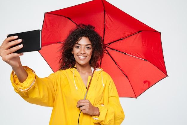 Glimlachende afrikaanse vrouw in regenjas die onder paraplu verbergt en selfie op haar smartphone over witte achtergrond maakt