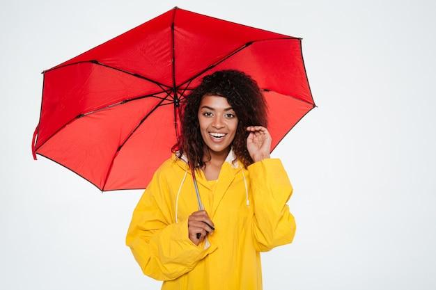 Glimlachende afrikaanse vrouw in regenjas het stellen met paraplu