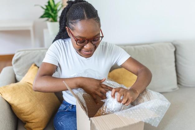 Glimlachende afrikaanse vrouw zit op de bank thuis open postpakket online winkelen goederen kopen op internet, gelukkige jonge vrouwelijke klant uitpakken postverzending pakket tevreden met bestelling of levering