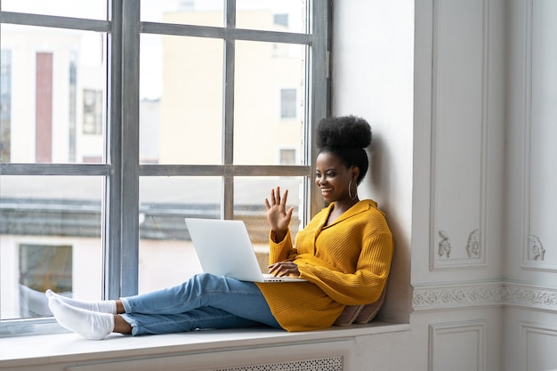 Glimlachende afrikaanse vrouw zittend op de vensterbank zeg hallo praten over videochat met vrienden op laptop