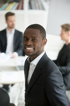 Glimlachende afrikaanse zakenman die pak headshot verticaal portret met team dragen