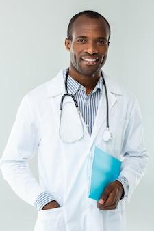 Glimlachende afro-amerikaanse arts die zich tegen witte muur bevindt terwijl hij een casusrapport vasthoudt