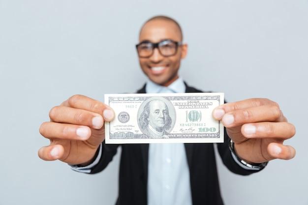 Glimlachende afro-amerikaanse jonge man in glazen met dollar biljet