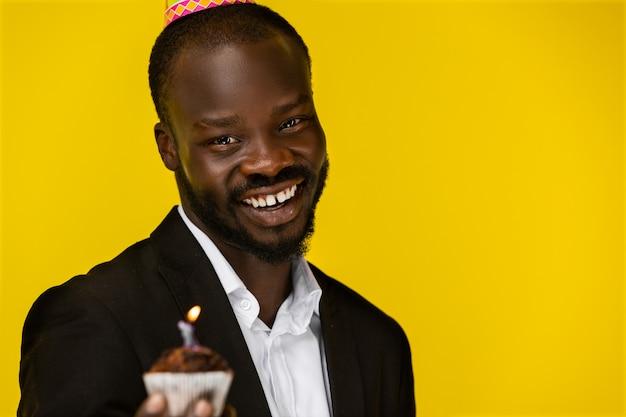 Glimlachende afro-amerikaanse kerel met brandende kaars