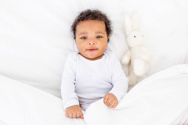 Glimlachende afro-amerikaanse kleine baby onder een deken met een stuk speelgoed op een wit bed om te slapen