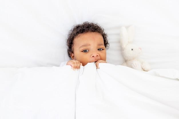 Glimlachende afro-amerikaanse kleine baby onder een deken met speelgoed op een wit bed om te slapen