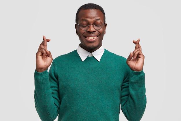 Glimlachende afro-amerikaanse man bidt voor de vervulling van zijn wens, kruist vingers, wenst veel succes
