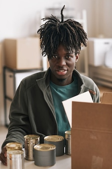 Glimlachende afro-amerikaanse man die ingeblikt voedsel in dozen verpakt terwijl hij vrijwilligerswerk deed bij liefdadigheids- en donatiesevenementen