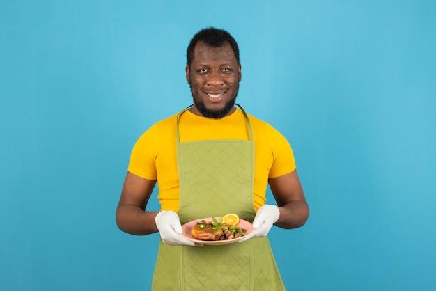 Glimlachende afro-amerikaanse man met baard die een schort draagt met een bord eten in de hand, staat over de blauwe muur.