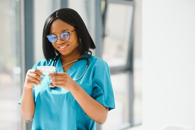 Glimlachende afro-amerikaanse verpleegster met de pil van de stethoscoopholding