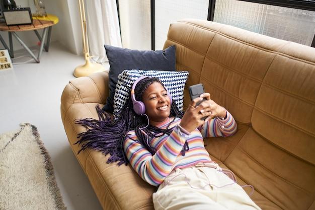 Glimlachende afro-amerikaanse vrouw die naar muziek luistert met een koptelefoon en een smartphone gebruikt die ontspannen op de ...