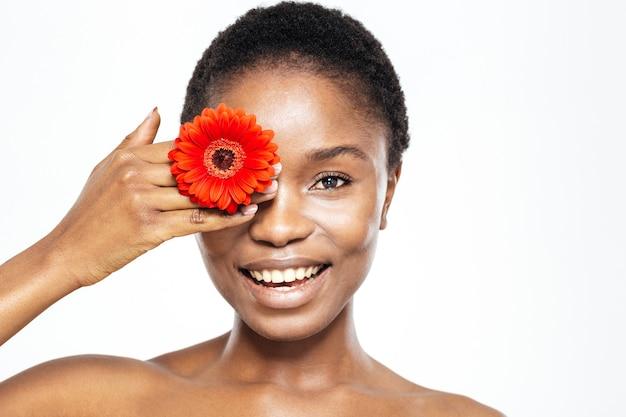 Glimlachende afro-amerikaanse vrouw die oog bedekt met bloem geïsoleerd op een witte achtergrond white