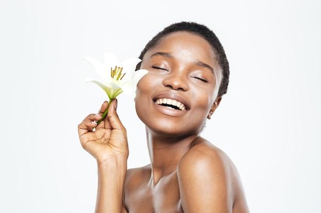 Glimlachende afro-amerikaanse vrouw met bloem geïsoleerd op een witte achtergrond