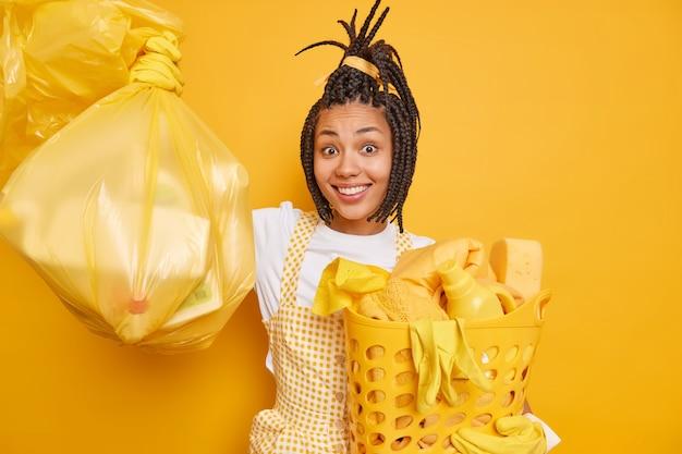 Glimlachende afro-amerikaanse vrouw met dreadlocks houdt van huishoudelijk werk en houdt polyethyleen tas vast