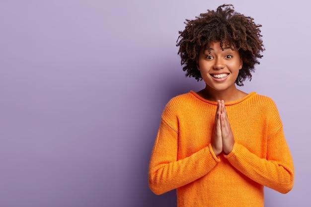 Glimlachende afro-amerikaanse vrouw smeekt om iets, houdt de handpalmen tegen elkaar gedrukt in een gebedgebaar, smeekt vrolijk