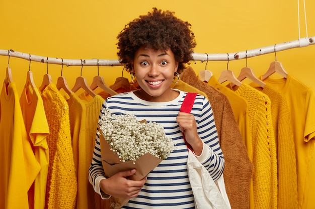 Glimlachende afro-amerikaanse vrouw vormt tegen kast, passende nieuwe outfit kiest, houdt van gele kleur, draagtas, houdt bloemen, glimlacht breed