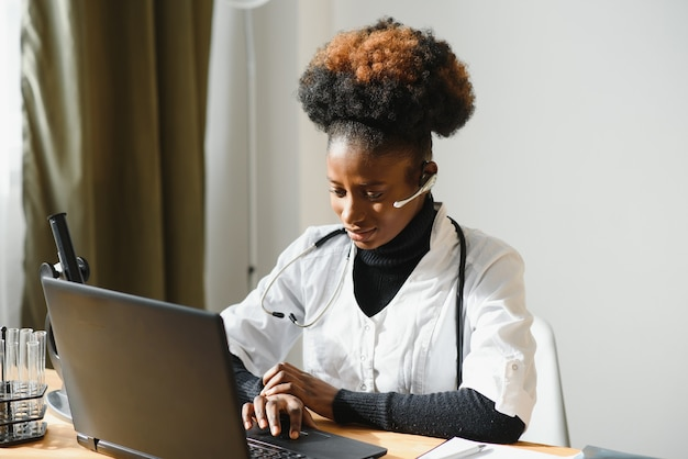 Glimlachende afro-amerikaanse vrouwelijke arts gp draagt witte medische jas met behulp van laptop op de werkplek.