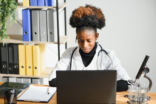 Glimlachende afro-amerikaanse vrouwelijke arts gp draagt witte medische jas met behulp van laptopcomputer.