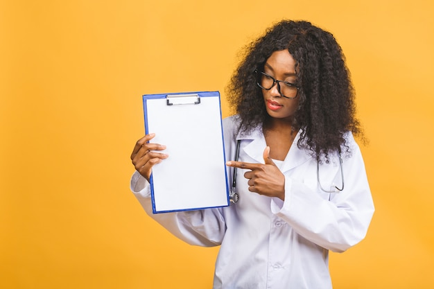 Glimlachende afro-amerikaanse vrouwelijke arts in witte jas met klembord en stethoscoop