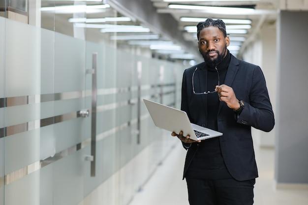 Glimlachende afro-amerikaanse zakenman die alleen staat in een groot kantoor met een foto van hoge kwaliteit