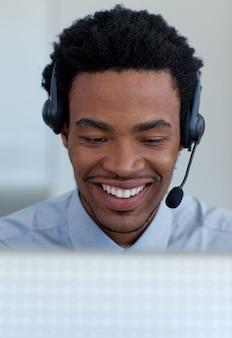 Glimlachende afro-amerikaanse zakenman die in een call centre spreekt