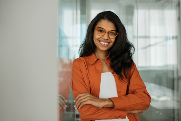 Glimlachende afro-amerikaanse zakenvrouw die een bril draagt en naar de camera kijkt