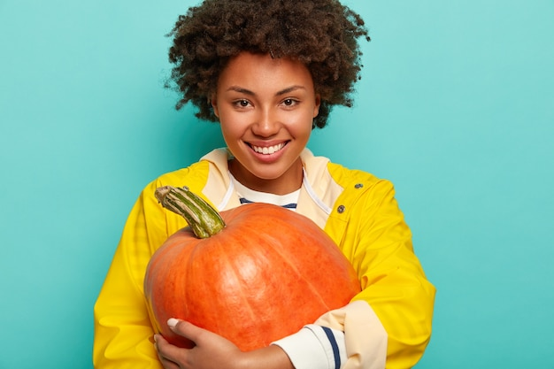 Glimlachende afro-vrouw houdt pompoen in de herfst, draagt gele beschermende regenjas, heeft een gelukkig humeur, staat tegen een blauwe achtergrond.