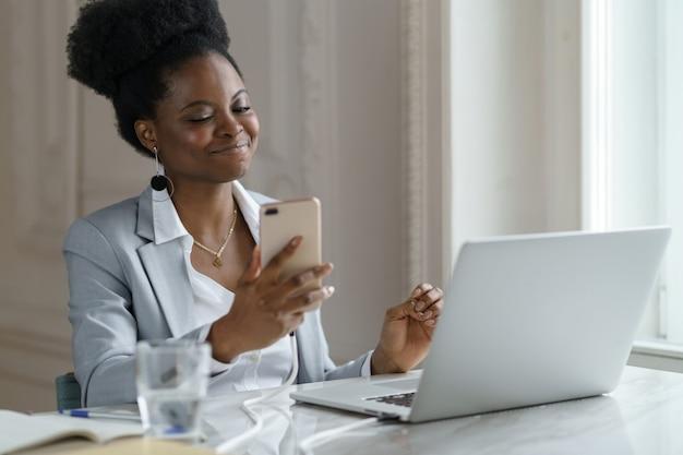 Glimlachende afro-vrouw neem een pauze, chatten met vriend over weekend in sociale media zittend op kantoor