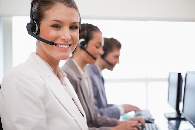 Glimlachende agentencollega's van het call centre achter haar