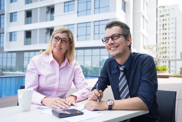 Glimlachende ambitieuze accountants die bij lijst met documenten en calculator zitten