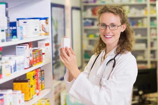 Glimlachende apotheker die kruik van plank neemt