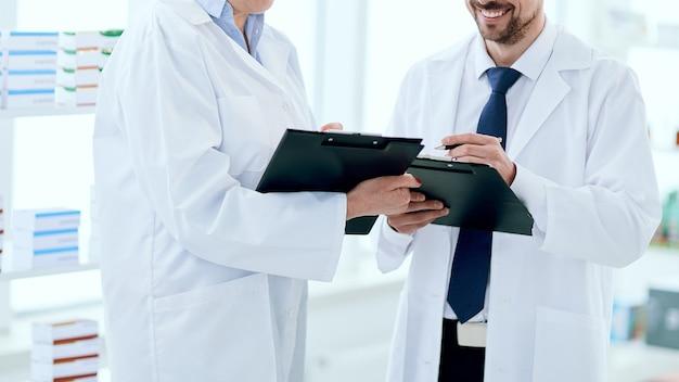 Glimlachende apothekers bespreken iets dat bij het schap staat met medicijnen
