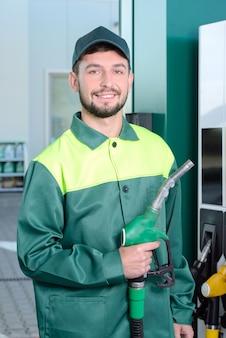 Glimlachende arbeider bij het benzinestation, terwijl het vullen van een auto