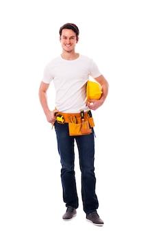 Glimlachende arbeider die gele bouwvakker houdt