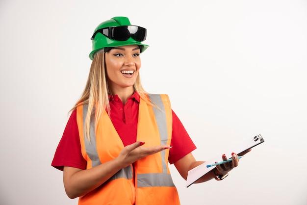 Glimlachende arbeidersvrouwenindustrie die een veiligheidsbril en veiligheidsuniform draagt