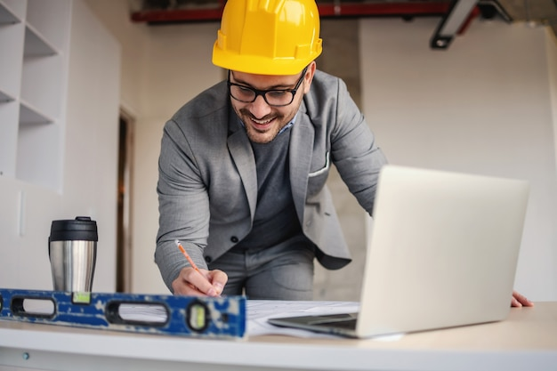 Glimlachende architect blauwdrukken tekenen op bouwplaats.