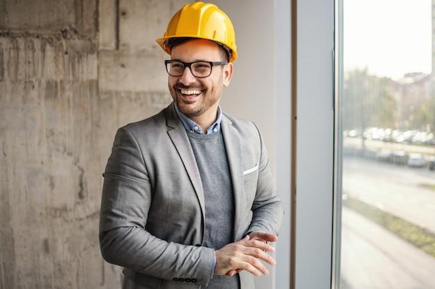 Glimlachende architect in pak die zich naast venster in bouw in bouwproces bevindt en weg kijkt.