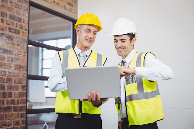 Glimlachende architecten die terwijl het houden van blauwdruk bespreken