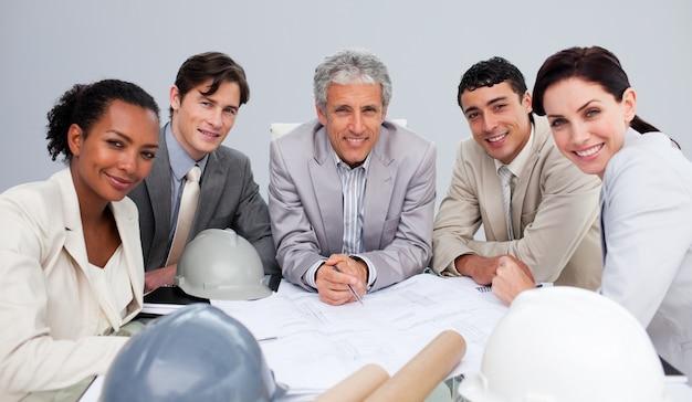 Glimlachende architecten in een vergadering die plannen bestudeert
