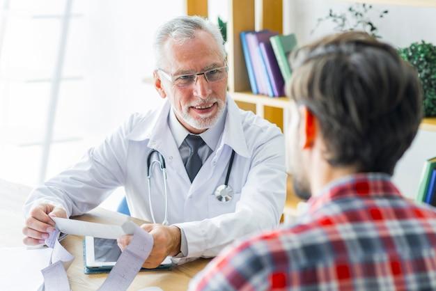 Glimlachende arts die aan patiënt luistert