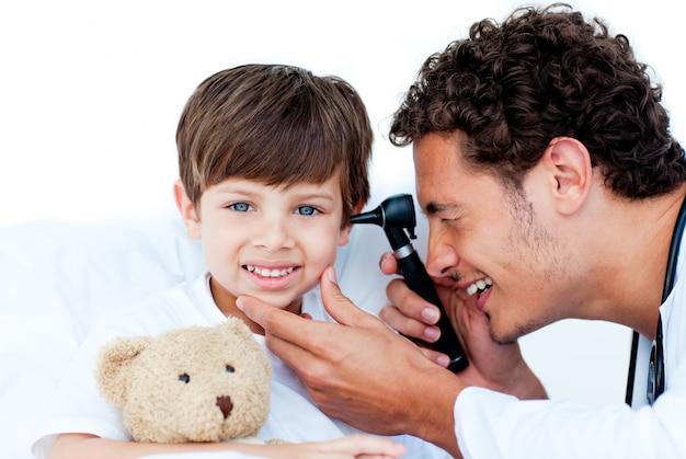 Glimlachende arts die de oren van de patiënt onderzoekt