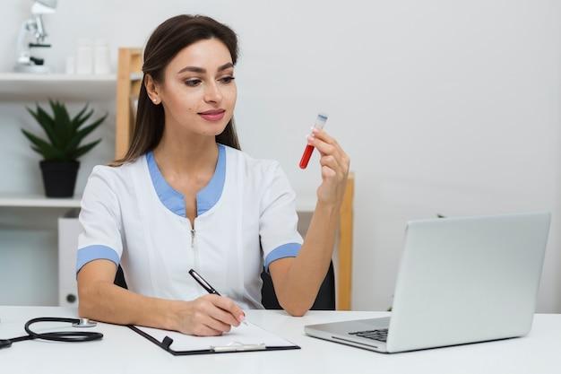 Glimlachende arts die een bloedmonster bekijkt