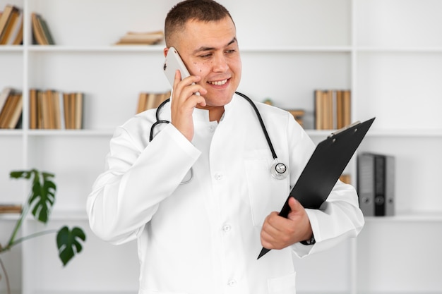 Glimlachende arts die een klembord houdt en op telefoon spreekt