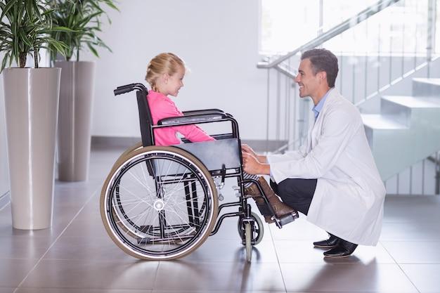 Glimlachende arts die meisje spreekt uit te schakelen