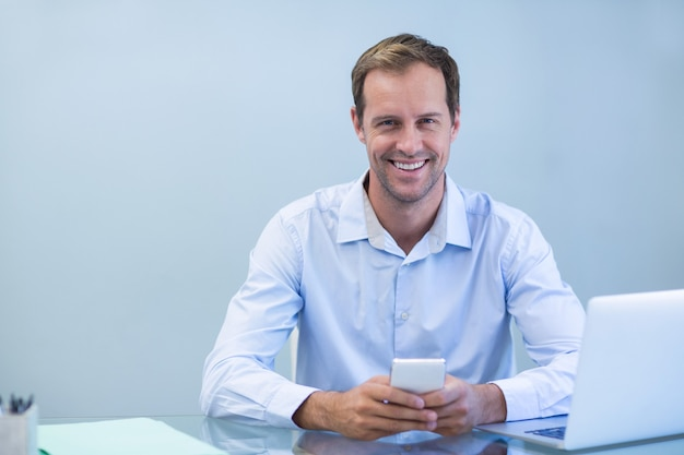 Glimlachende arts die mobiele telefoon in tandkliniek met behulp van