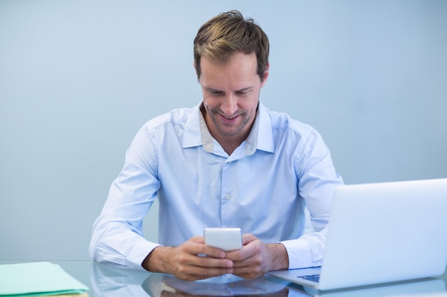 Glimlachende arts die mobiele telefoon met behulp van