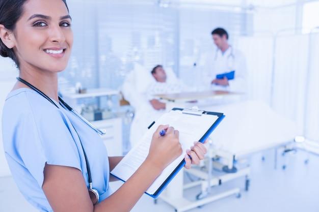 Glimlachende arts die patiëntendossier controleert